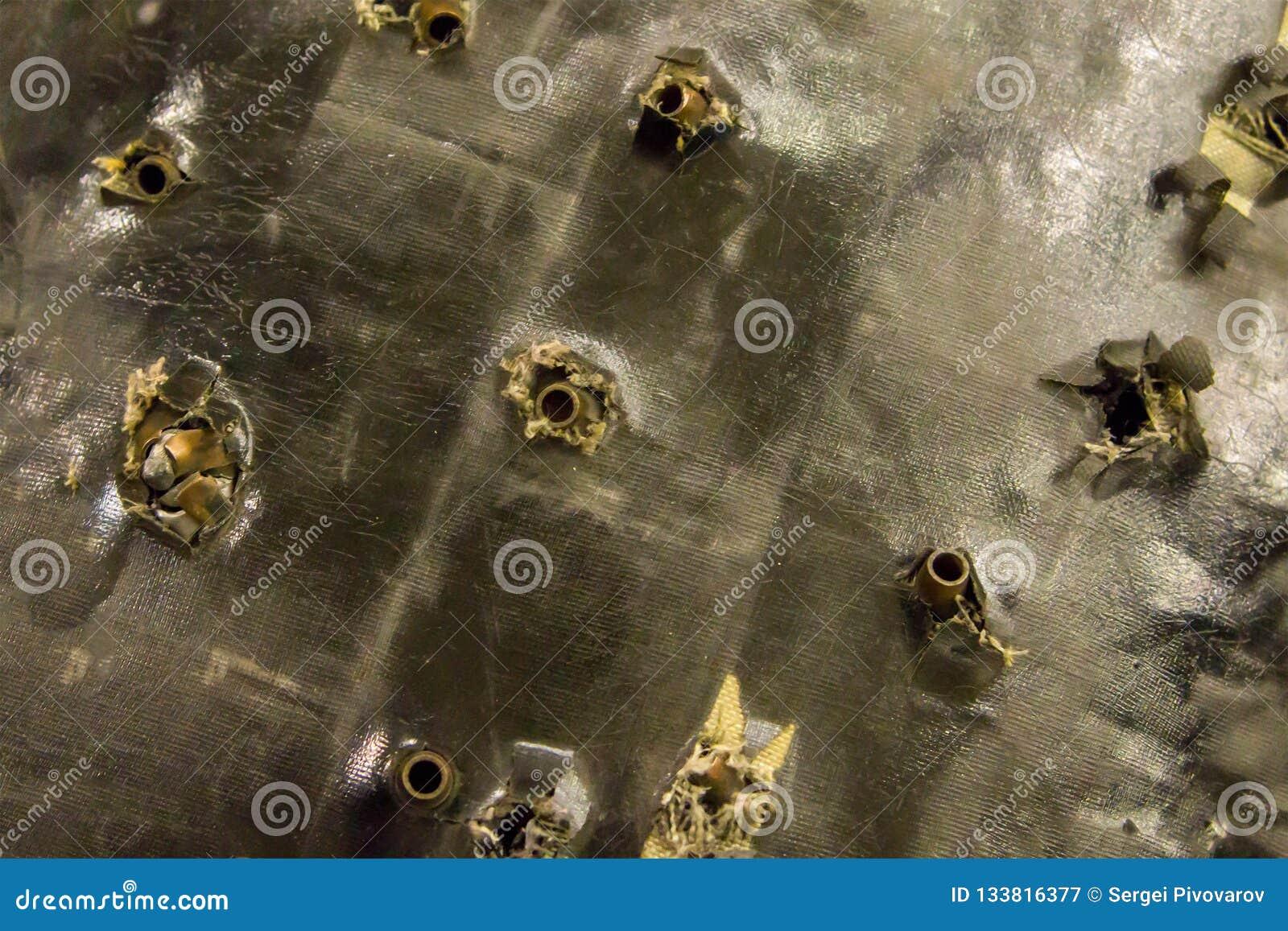 Fundo do Grunge superfície de muitas balas dos escudos de uma segurança perfurada quebrada velha do salvamento da veste à prova d