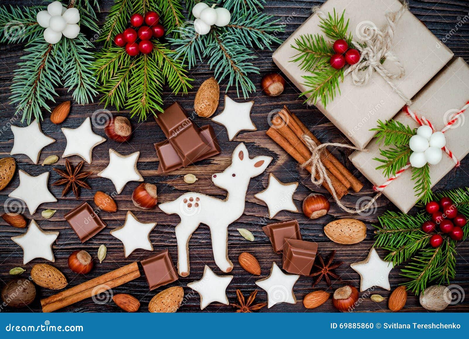 Fundo do Natal com cookies do pão-de-espécie, presentes, ramos do abeto e especiarias na placa de madeira velha