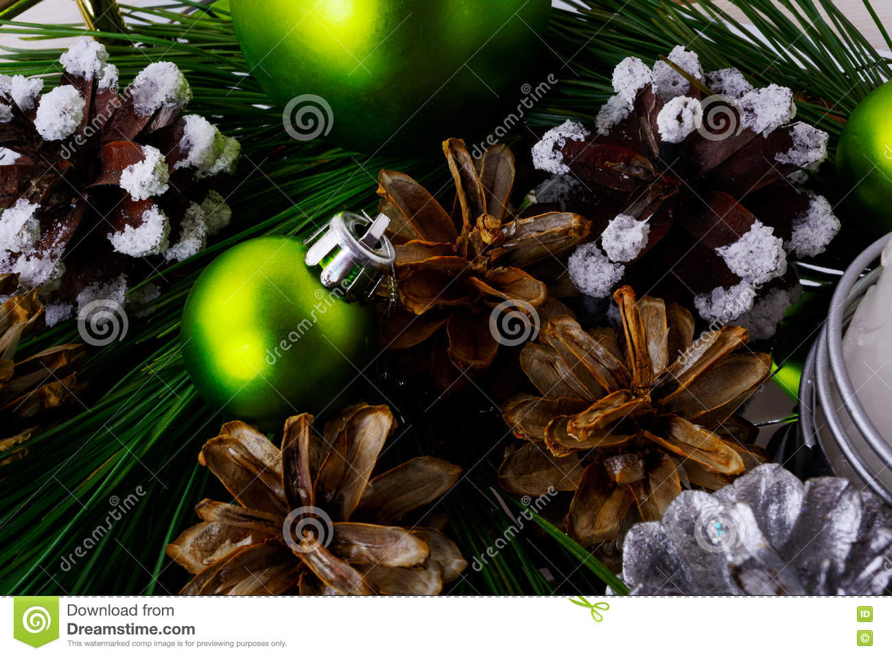 Fundo do Natal com pinecone nevado e os ornamento verdes