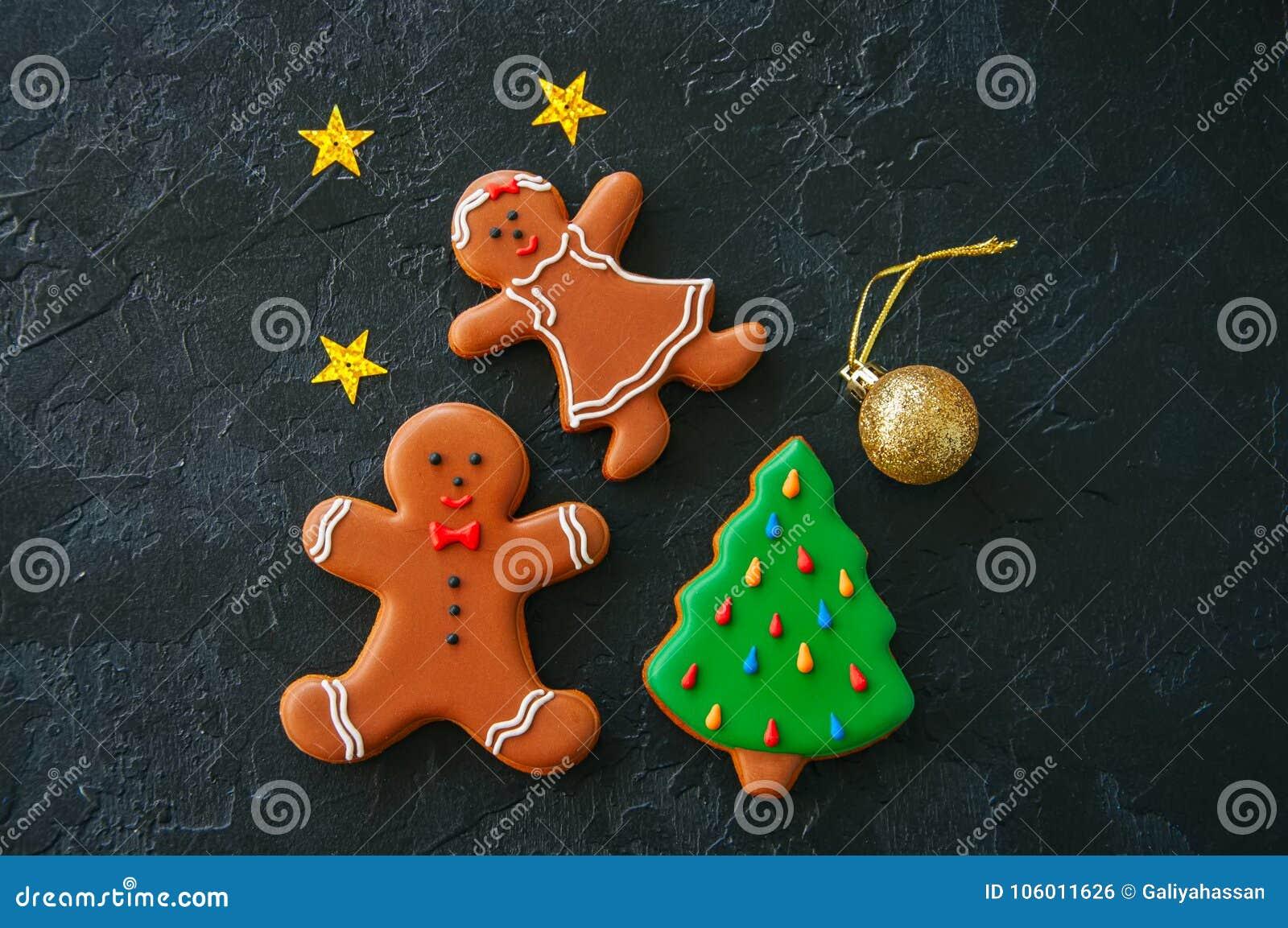 Fundo do Natal, homem de pão-de-espécie e cookies festivos da menina,