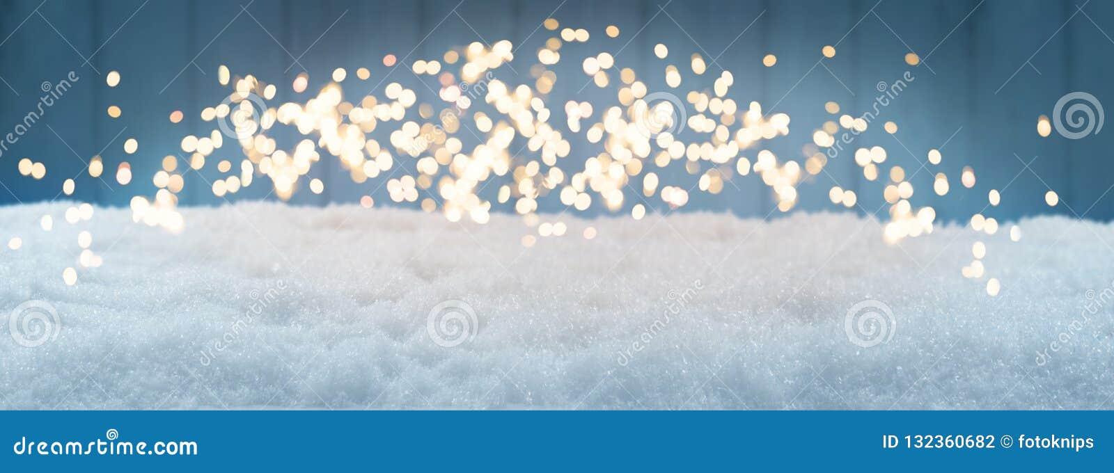 Fundo do Natal, neve com bokeh contra o azul