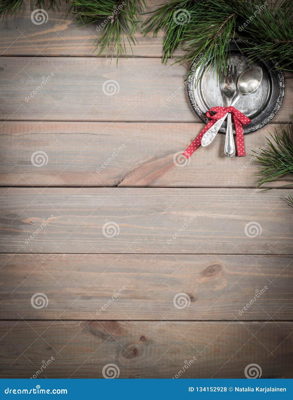 Fundo do Natal Tabela, ramo do pinho e artigos de madeira antigos do vintage Bandeja, forquilha de prata e colher, amarradas com