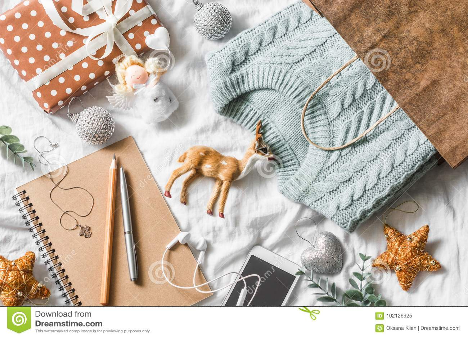 Fundo do planeamento e da compra do Natal O azul fez malha a camiseta em um saco de papel, bloco de notas, telefone, decoração do