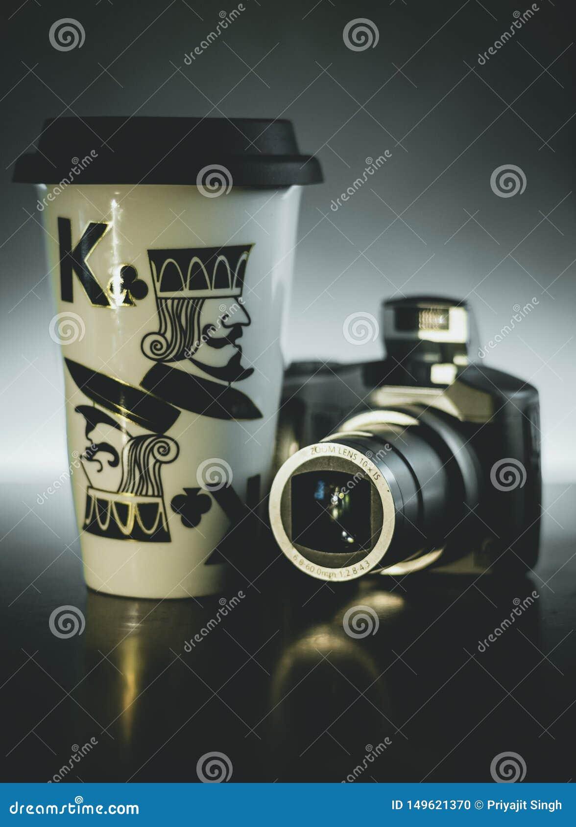 Fundo escuro da luz da c?mara digital da caneca de caf?