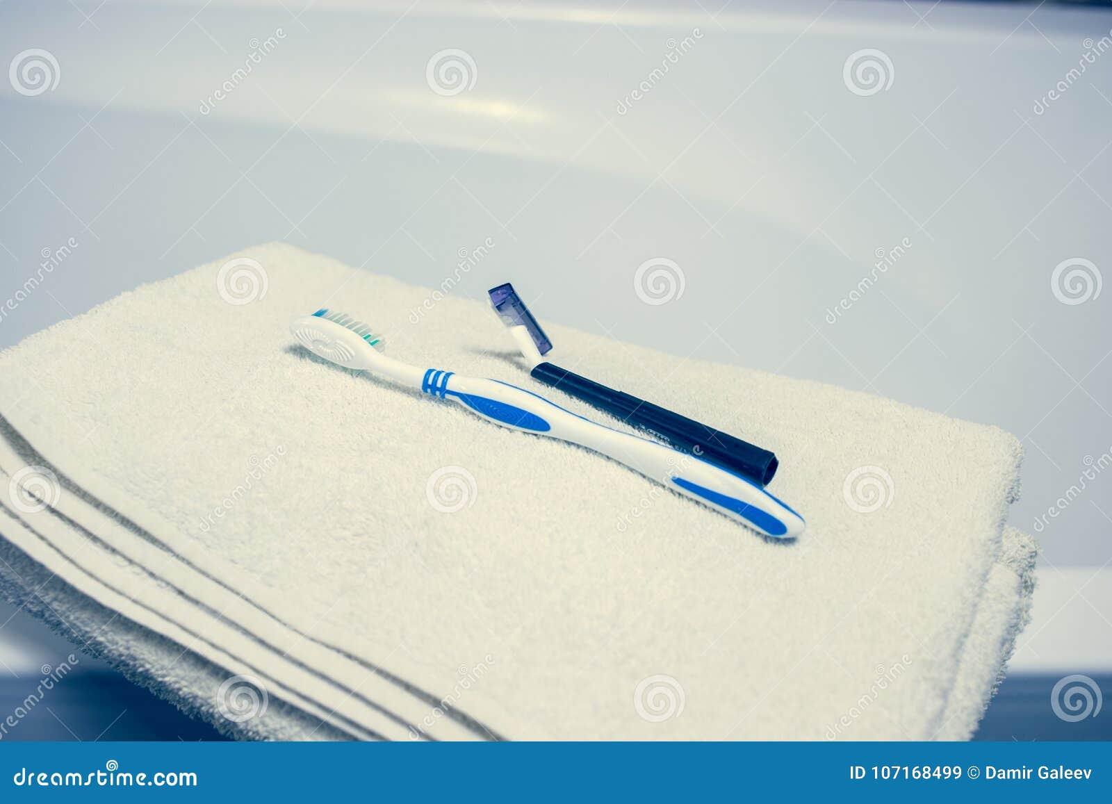 Fundo interior borrado do banheiro e toalhas brancas dos termas na lâmina de mármore da escova de dentes