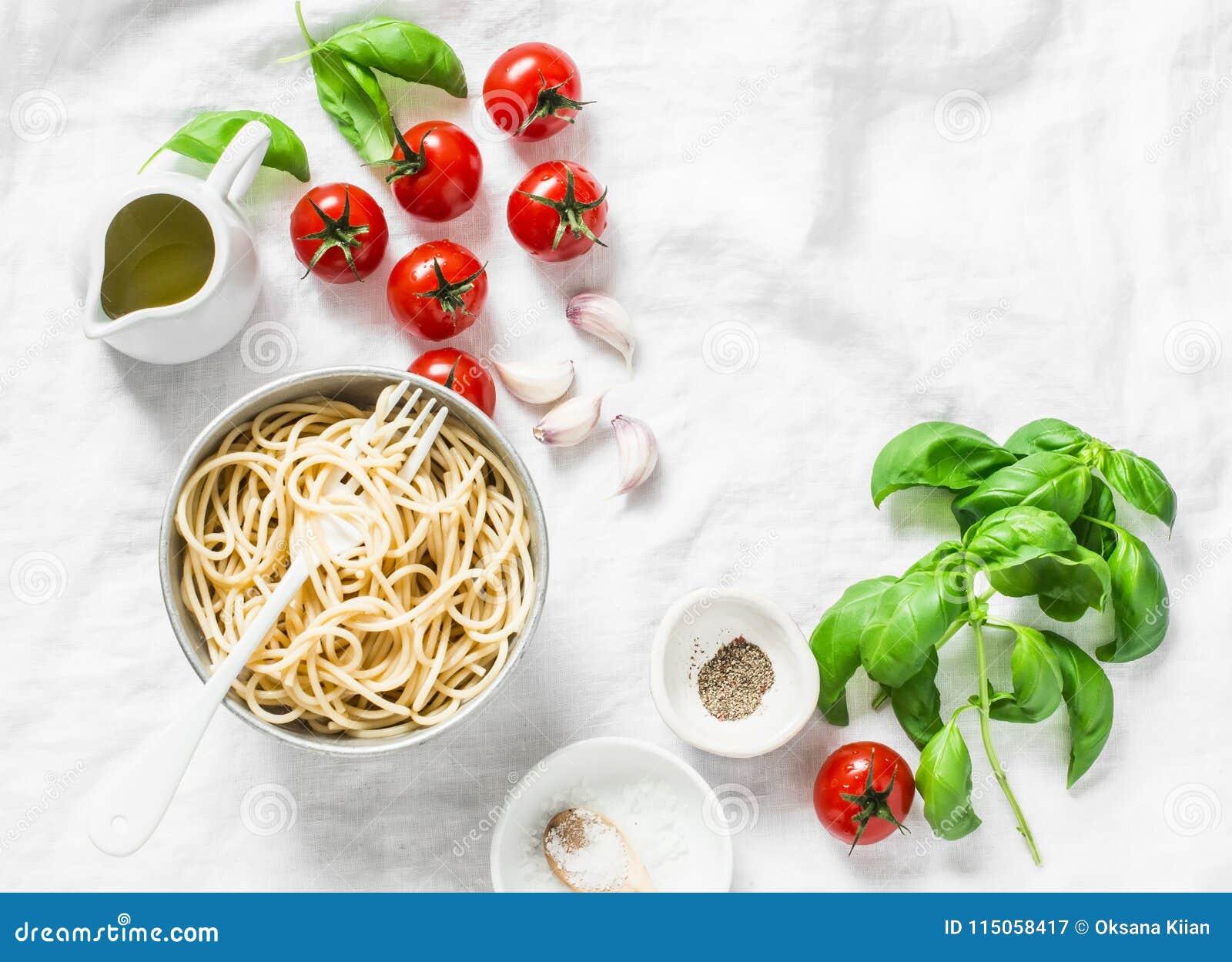 Fundo italiano da massa do alimento com espaço da cópia no fundo branco, vista superior Manjericão, espaguete inteiro da grão, to