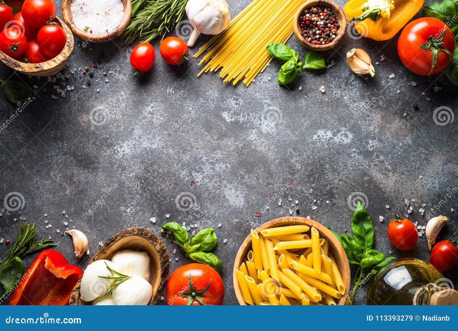 Fundo italiano do alimento Massa, ervas, vegetais na parte superior preta v