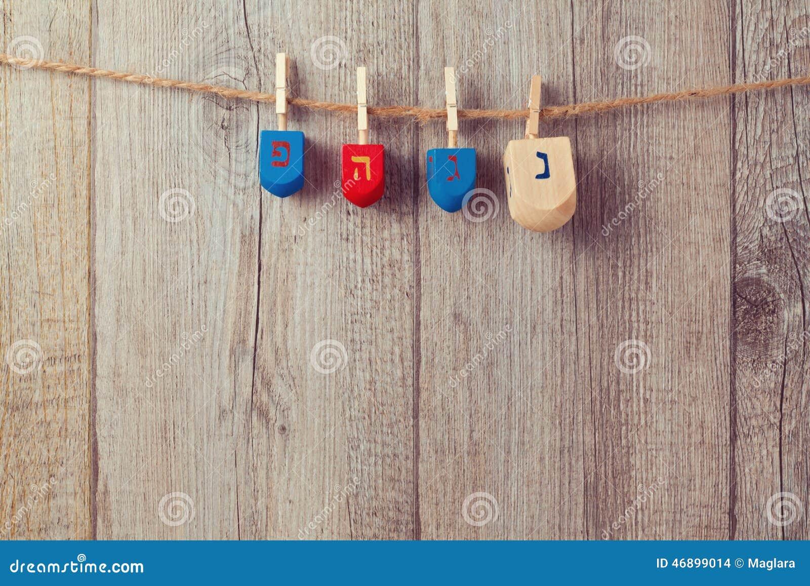 Fundo judaico do Hanukkah do feriado com a parte superior de giro de madeira do dreidel que pendura na corda