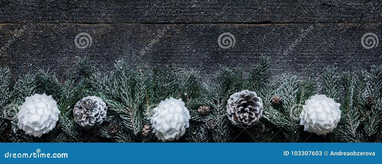 Fundo nevado do Natal, ramos de árvore do abeto com cones do pinho e quinquilharias do Xmas no fundo de madeira