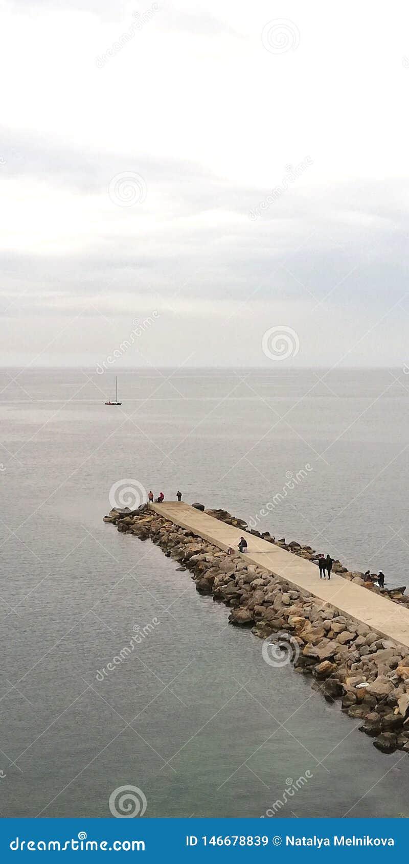 Fundo Paisagem da noite do mar Na alameda de pedra são as silhuetas visíveis dos povos