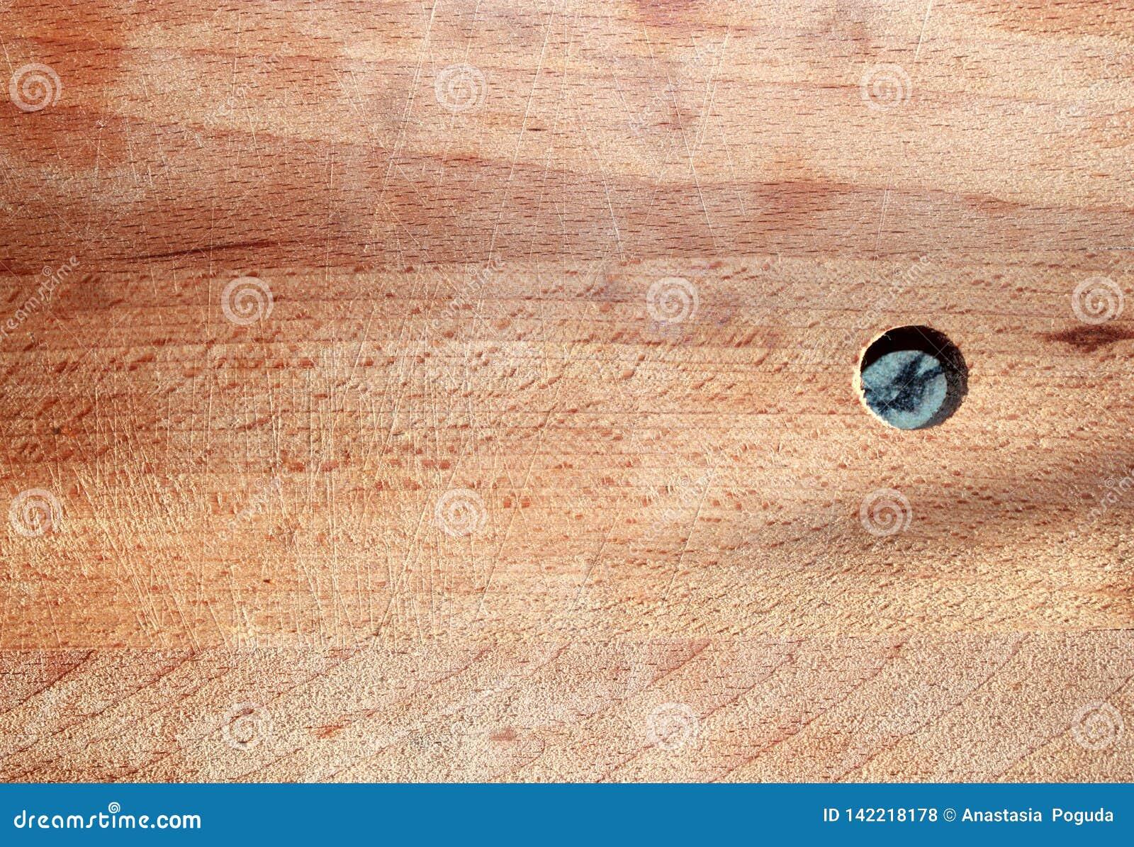 Fundo velho de madeira da placa de corte com marcas da faca e um furo redondo