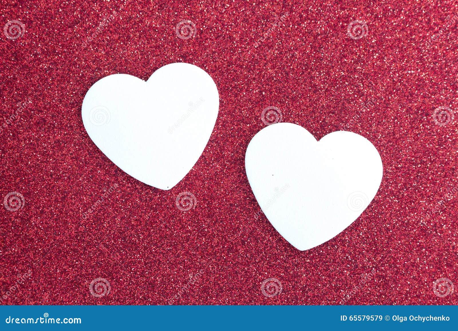 Fundo vermelho do brilho e dois corações brancos