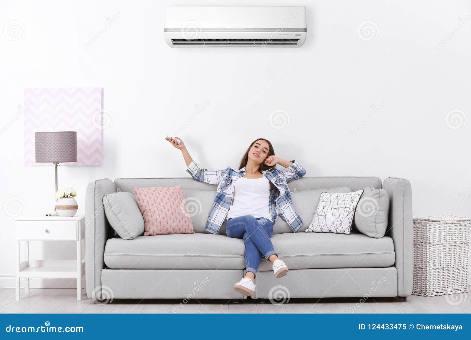 Fungerande luftkonditioneringsapparat för ung kvinna, medan sitta
