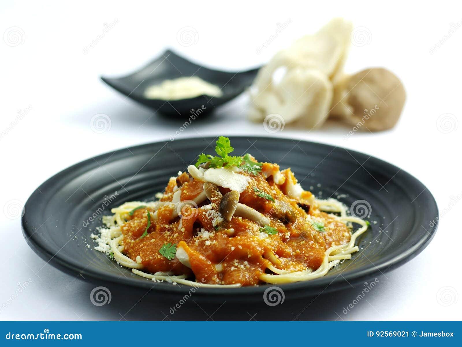 Fungo sauteed con la salsa di pomodori e la tagliatella di ramen sulla d nera