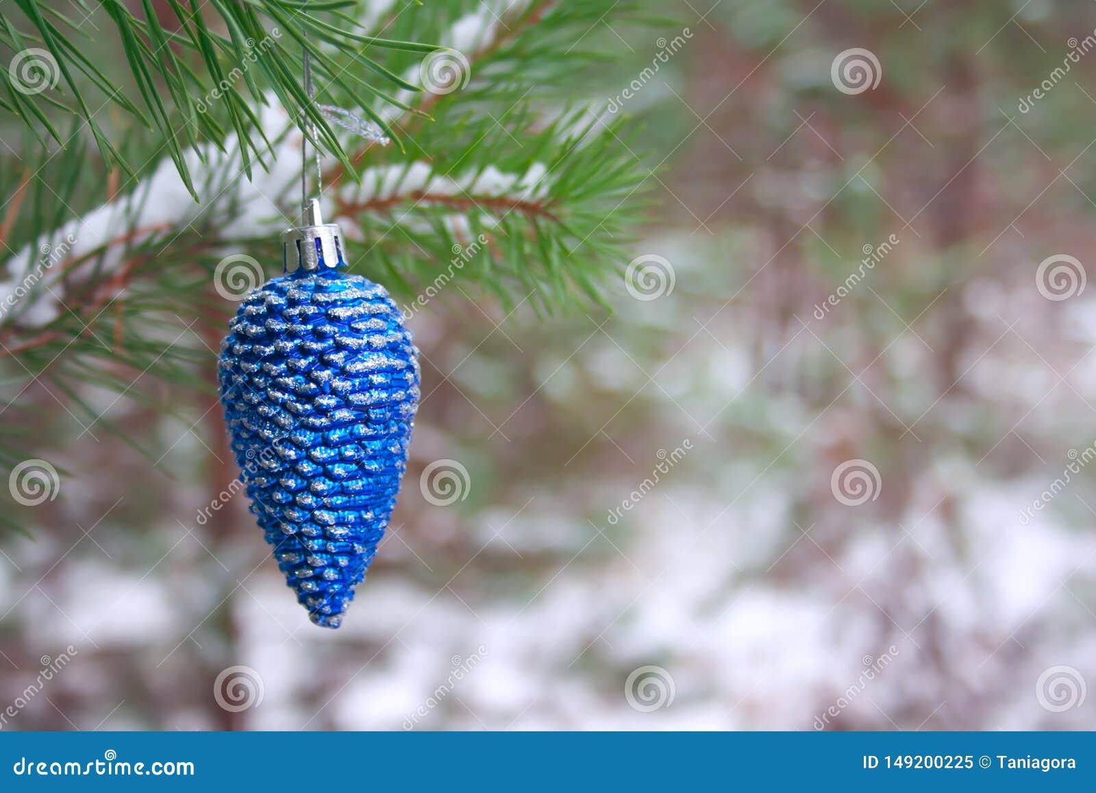 Funkelnder blauer Weihnachtsbaum-Spielzeugkegel auf einer Kiefernniederlassung in einem schneebedeckten Wald des Winters