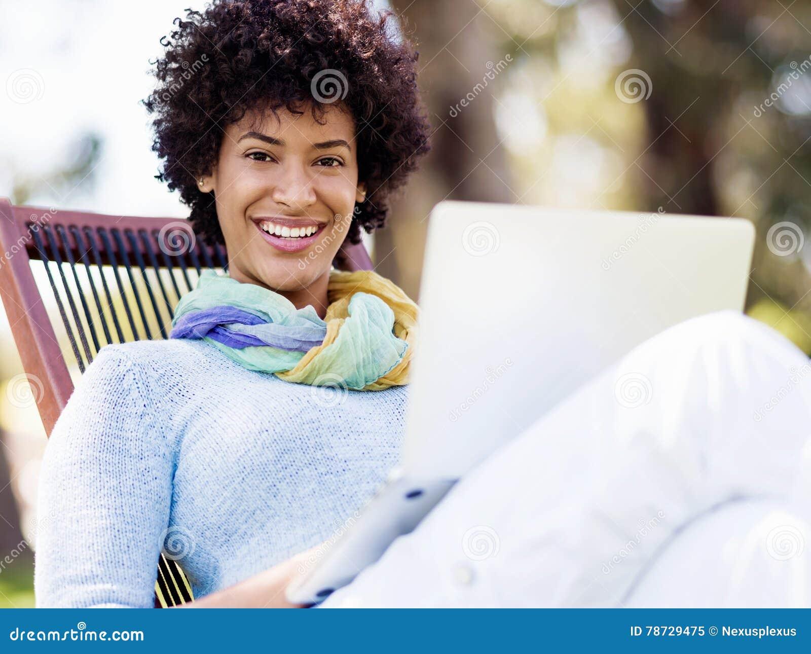 Funktionsduglig det fria för kvinna i en äng med bärbara datorn
