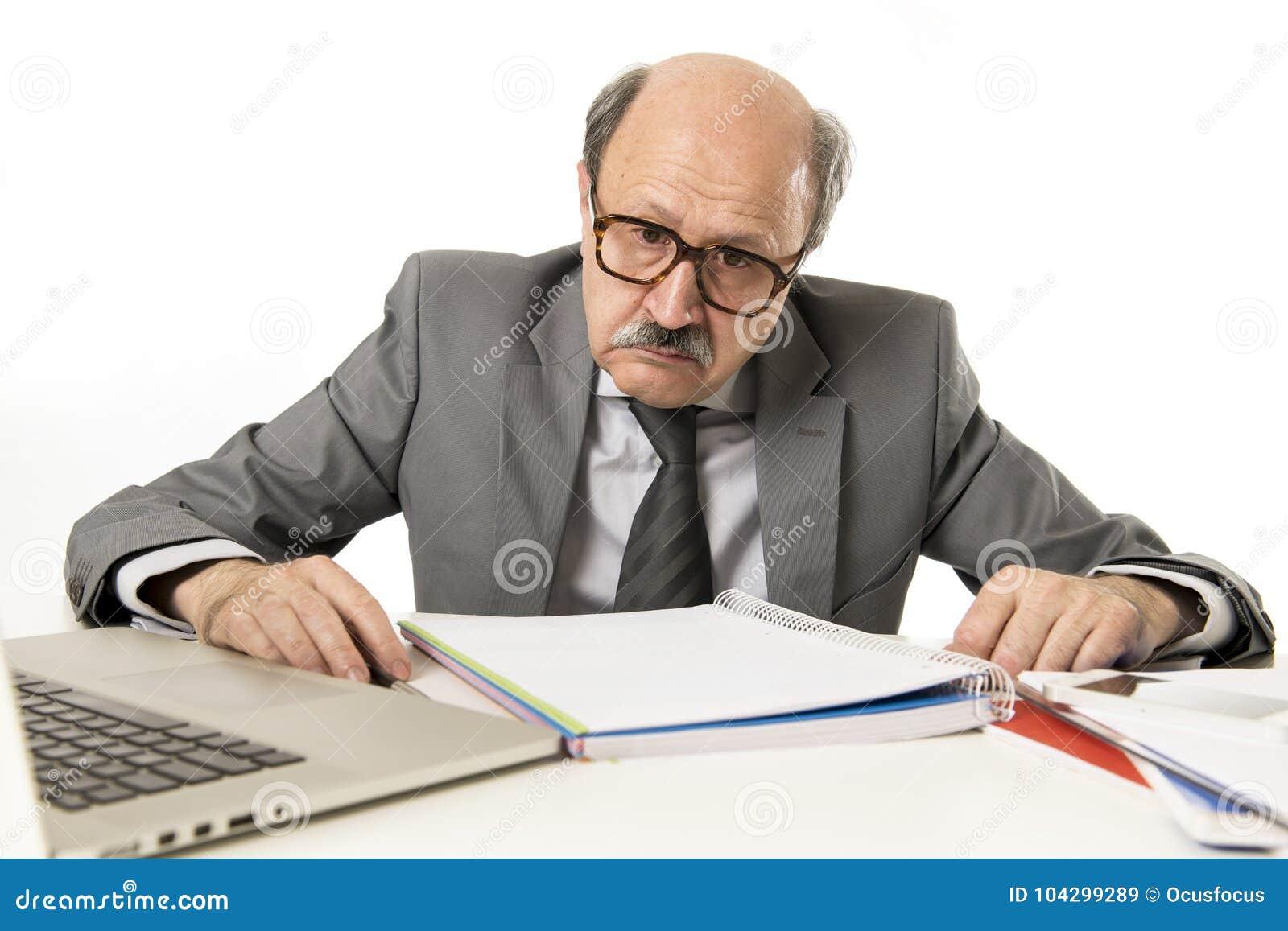 Funktionsduglig stressat för skallig 60-tal för affärsman och frustrerat på skrivbordet för bärbar dator för kontorsdator som ser