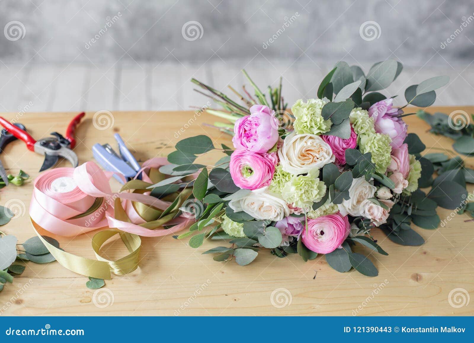 Funktionsduglig tabell i blomsterhandel Flickaassistent eller ägare i studio för blom- design och att göra garneringar och ordnin
