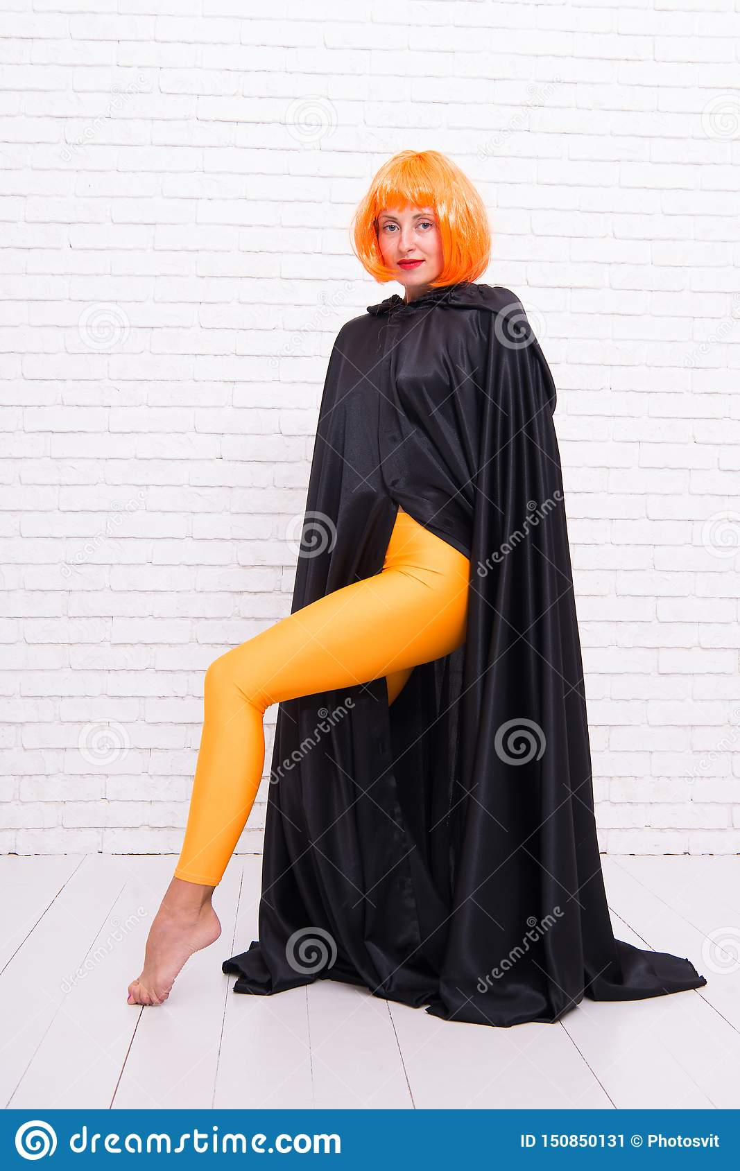 Funky style beauty. Sensual woman in fashion style on white brickwall. Fashion model wearing orange wig hair style and