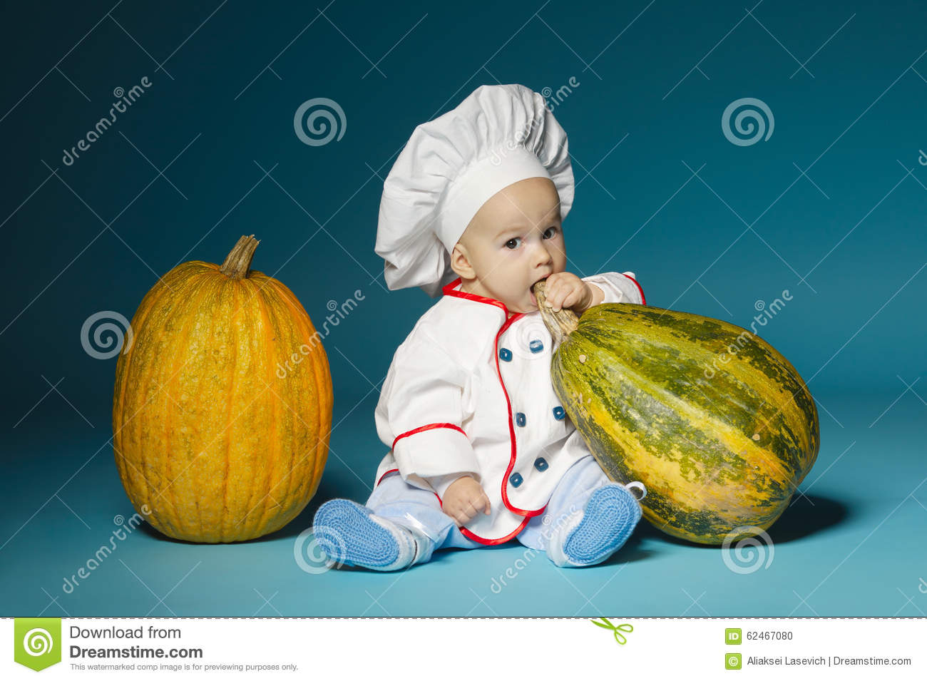 Funny baby with cook costume holds pumpkin