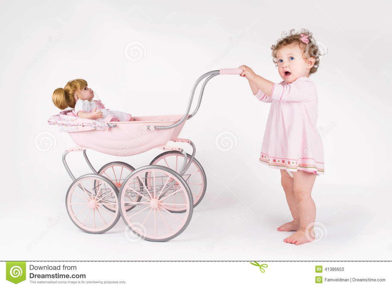 Funny baby girl walking with a doll stroller