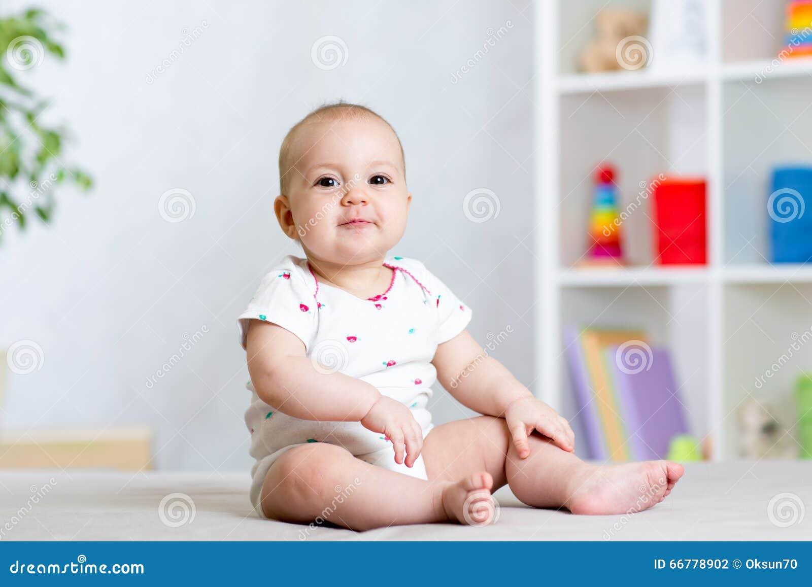 Funny baby kid girl sitting on floor in children room