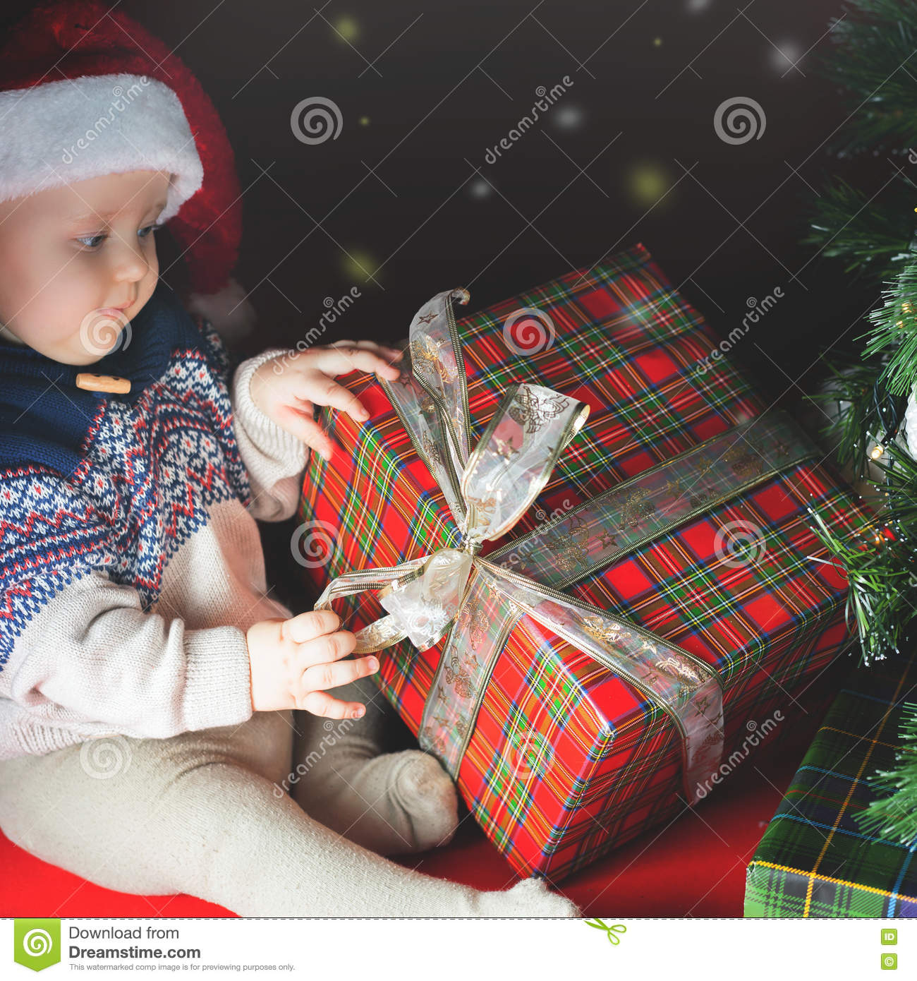 Funny Baby Opening Gift Box At Christmas. Dressed Santa Hat Stock ...
