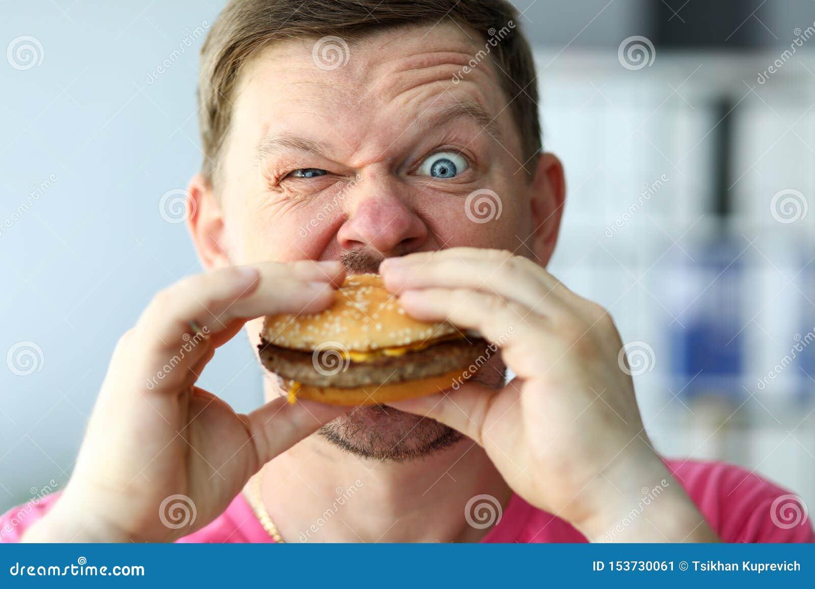 Funny bearded man with idiot facial expression eating big burger