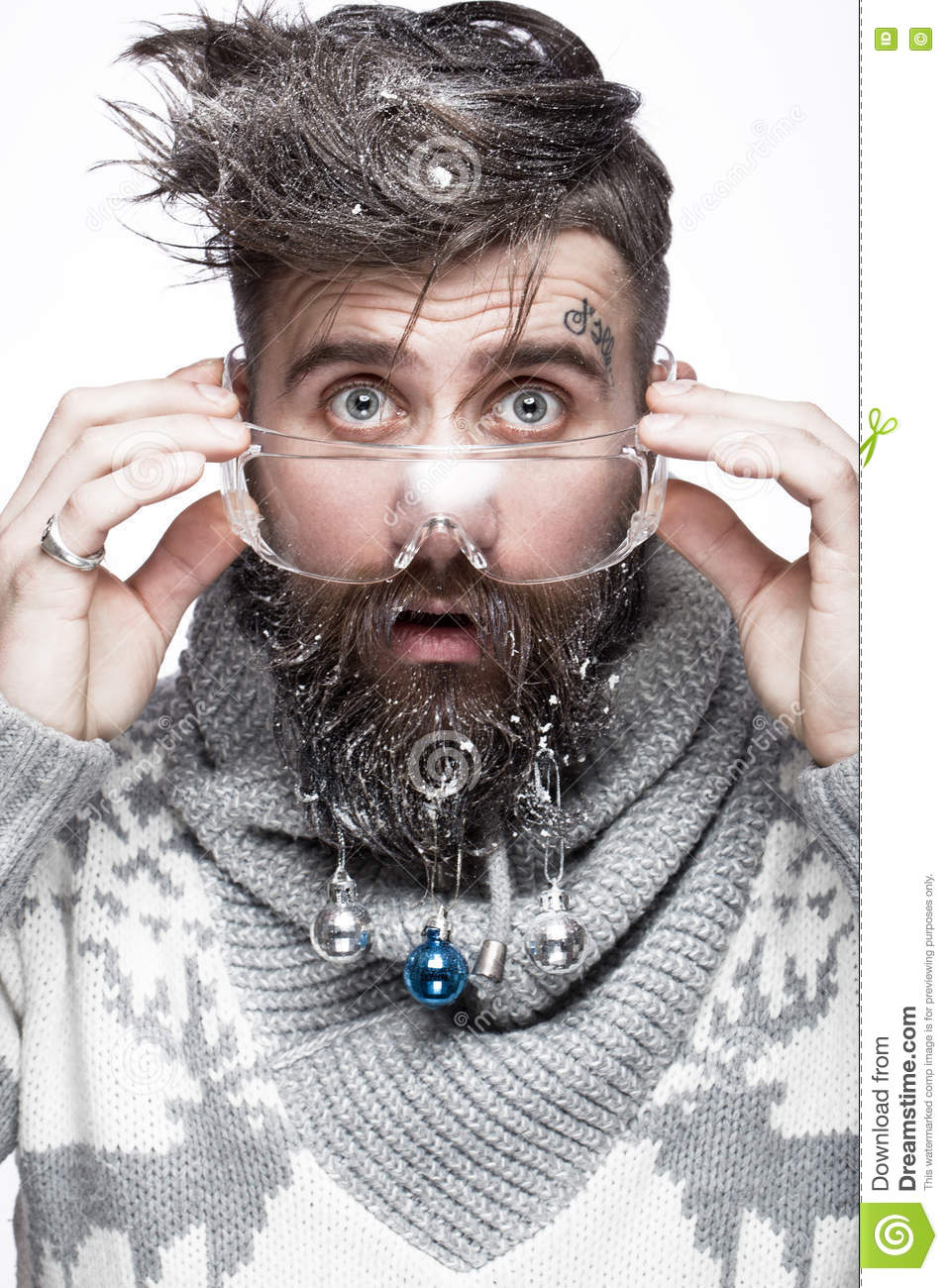 Funny bearded man in a New Year`s image with snow and decorations on his beard. Feast of Christmas.