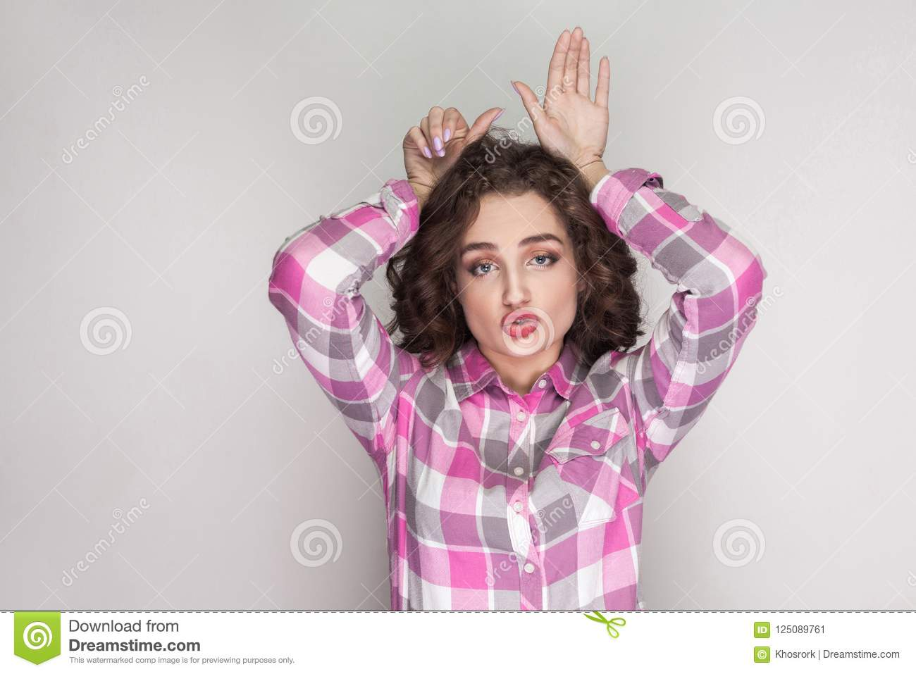 Funny beautiful girl with pink checkered shirt, curly hairstyle