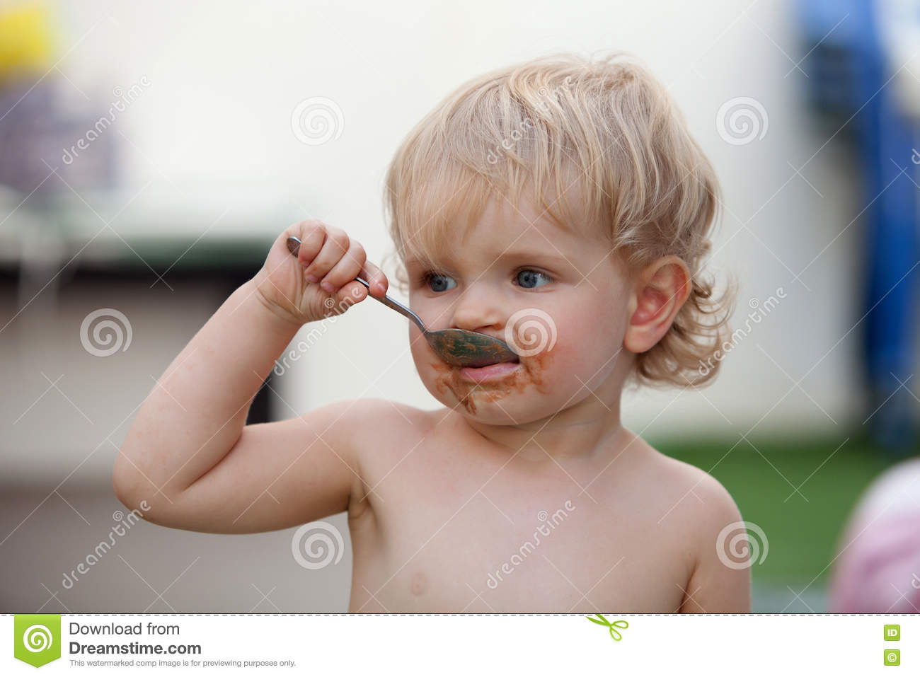 Funny blond baby eating chocolate