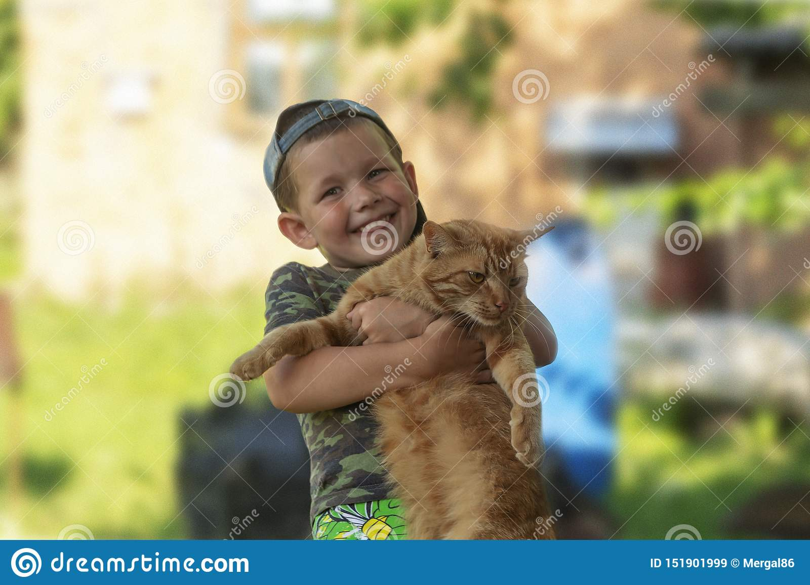 Funny boy hugging a cat with lots of love. Portrait of child holding on hands a big cat. playing with a cat