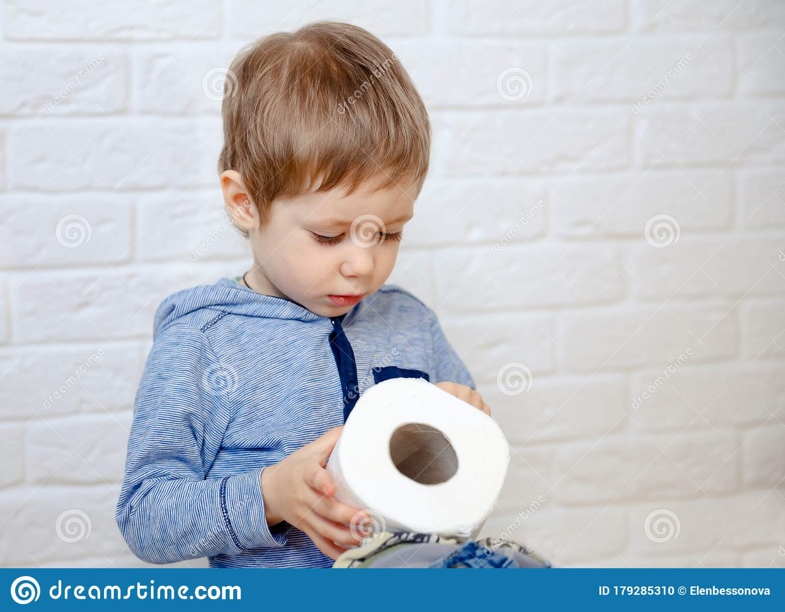 Portrait Of Little Boy Sitting On Against White Background