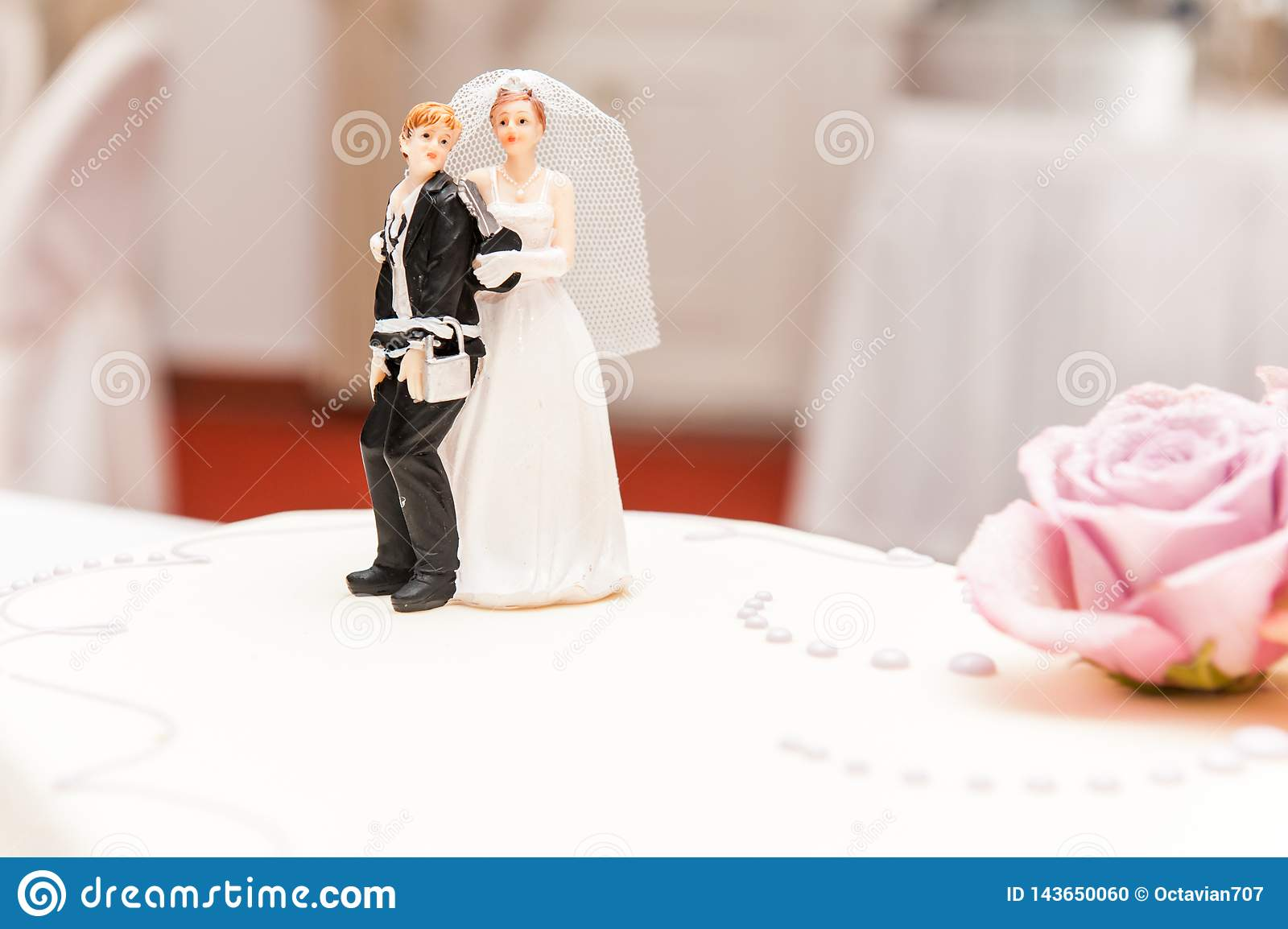 Funny bride and groom made of sugar on top of wedding cake