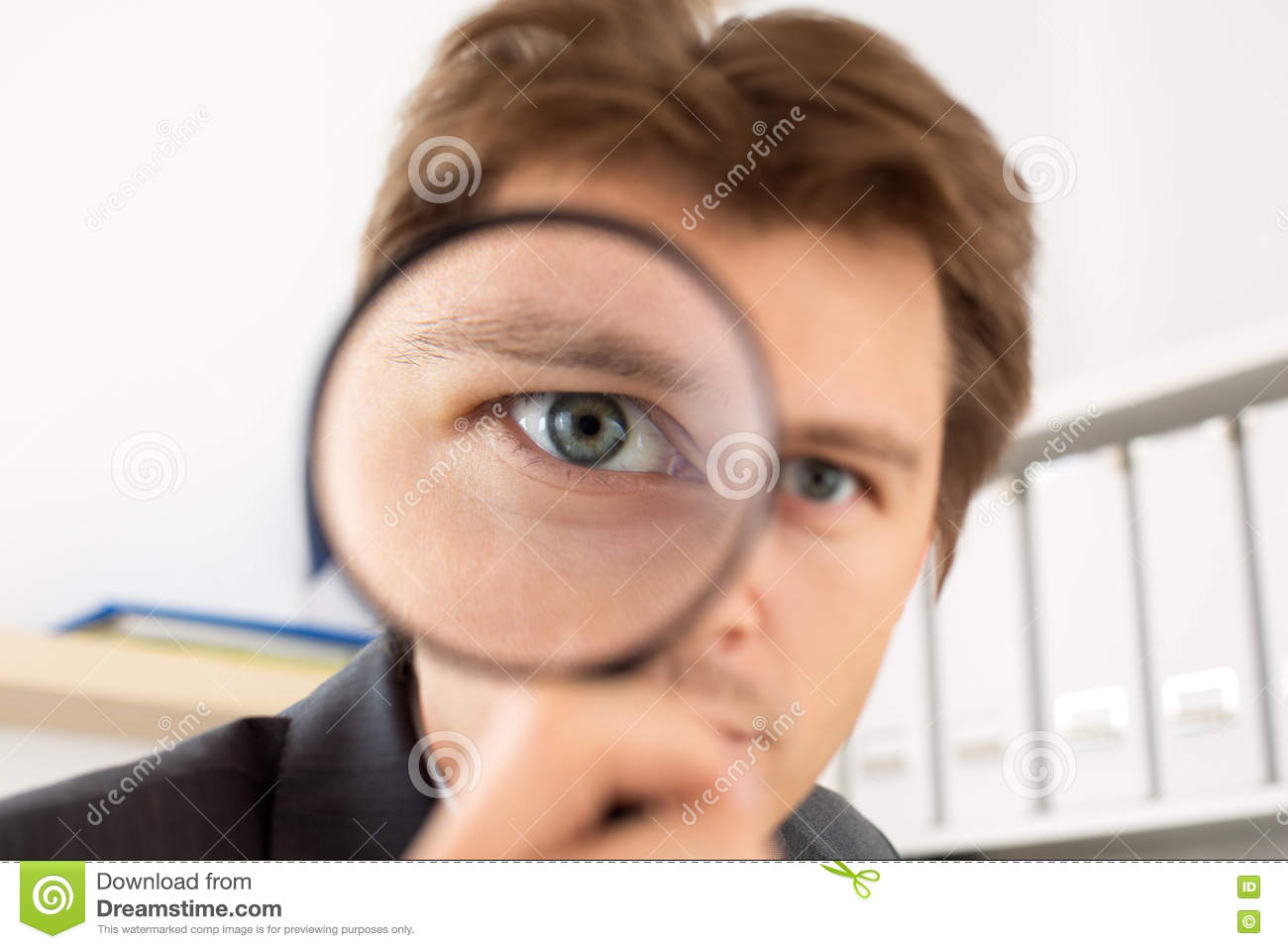 Funny business man holding magnifying glass