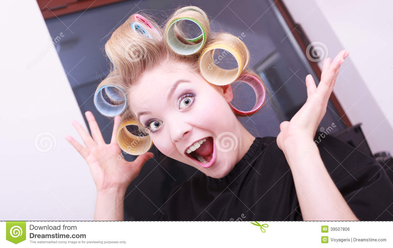 Funny cheerful blond girl hair curlers rollers by hairdresser in salon