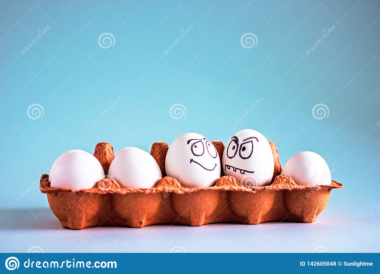 Funny chicken white eggs with faces in an egg cell.