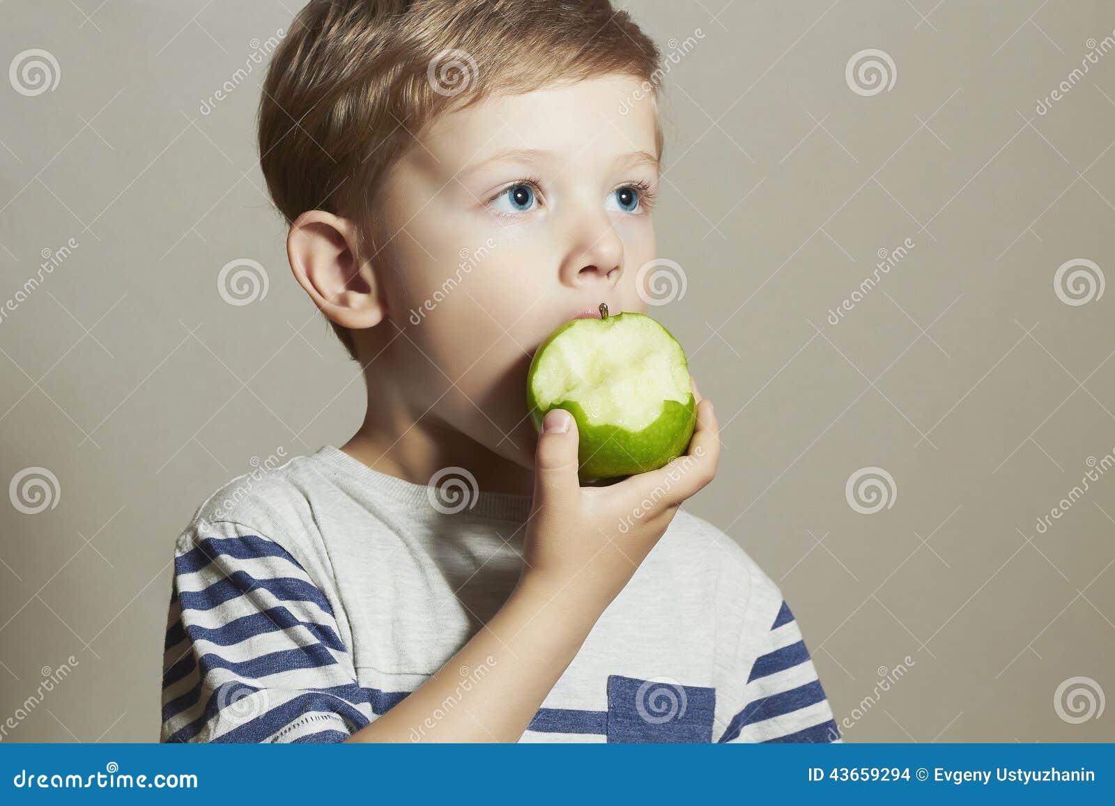 Funny Child eating apple.Little Boy. Health food. Fruits