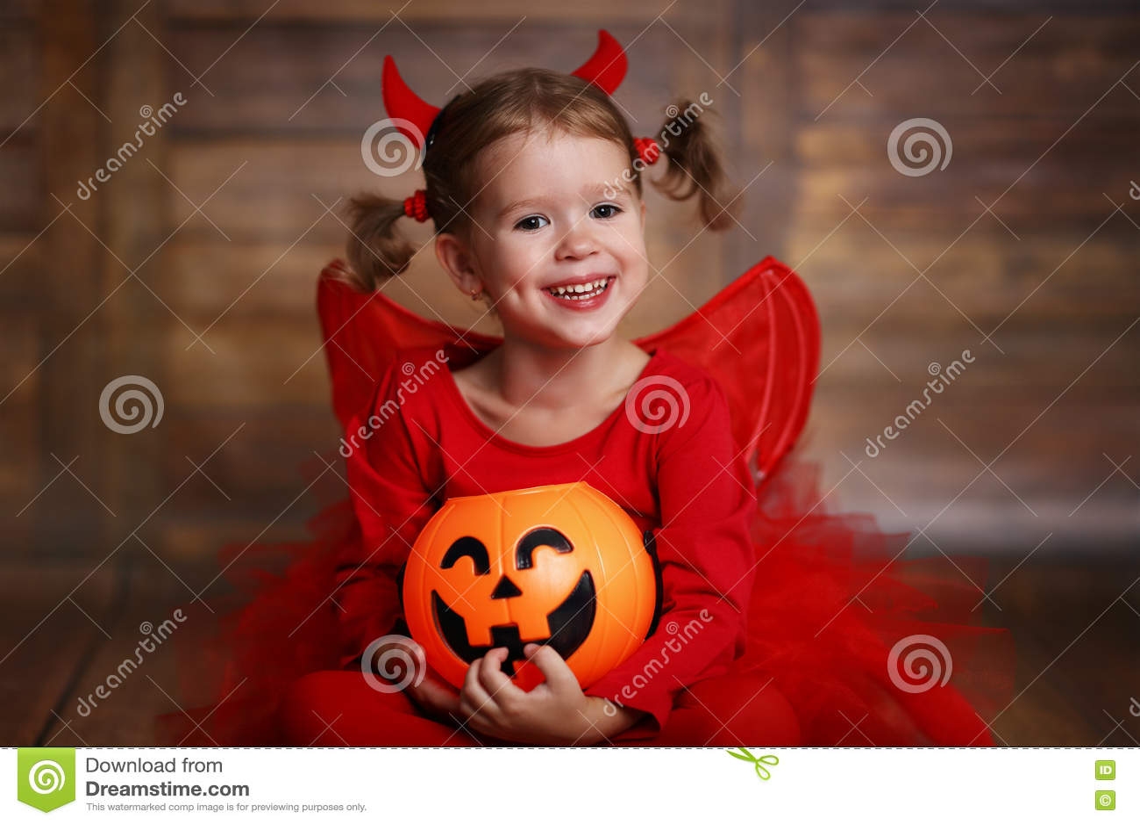 Funny Kids Halloween Costumes.Funny Child Girl In Devil Halloween Costume On Dark Wooden