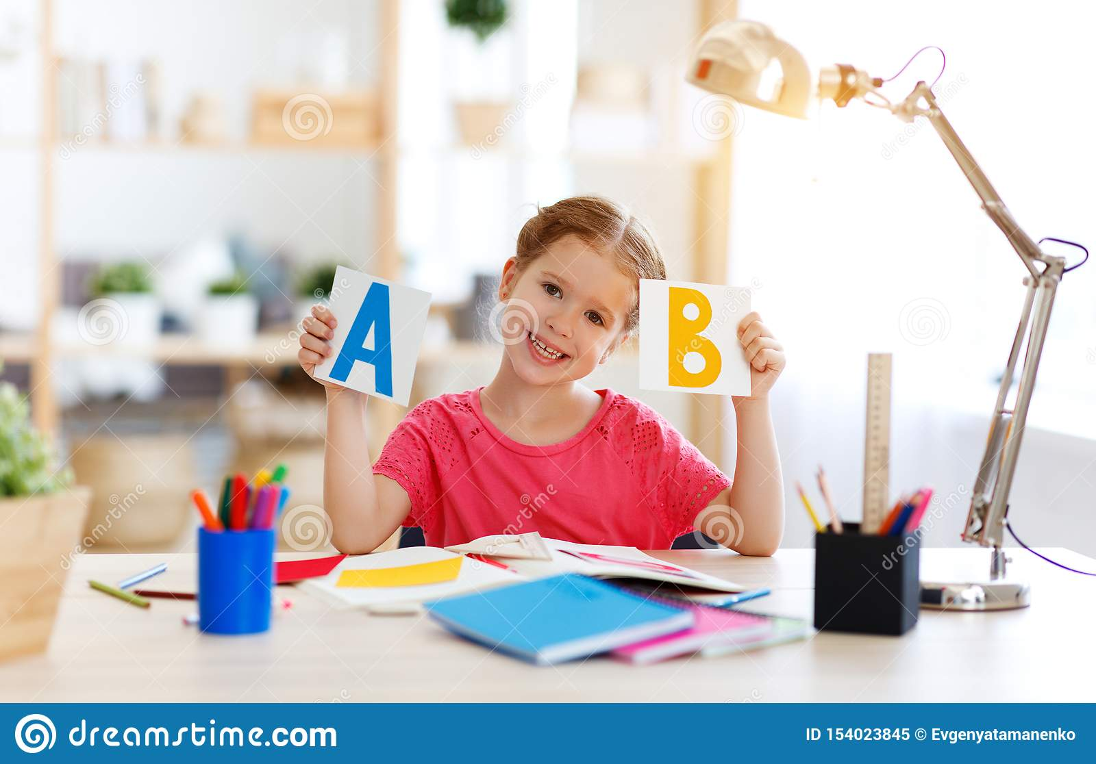 Funny child girl doing homework writing and reading at home