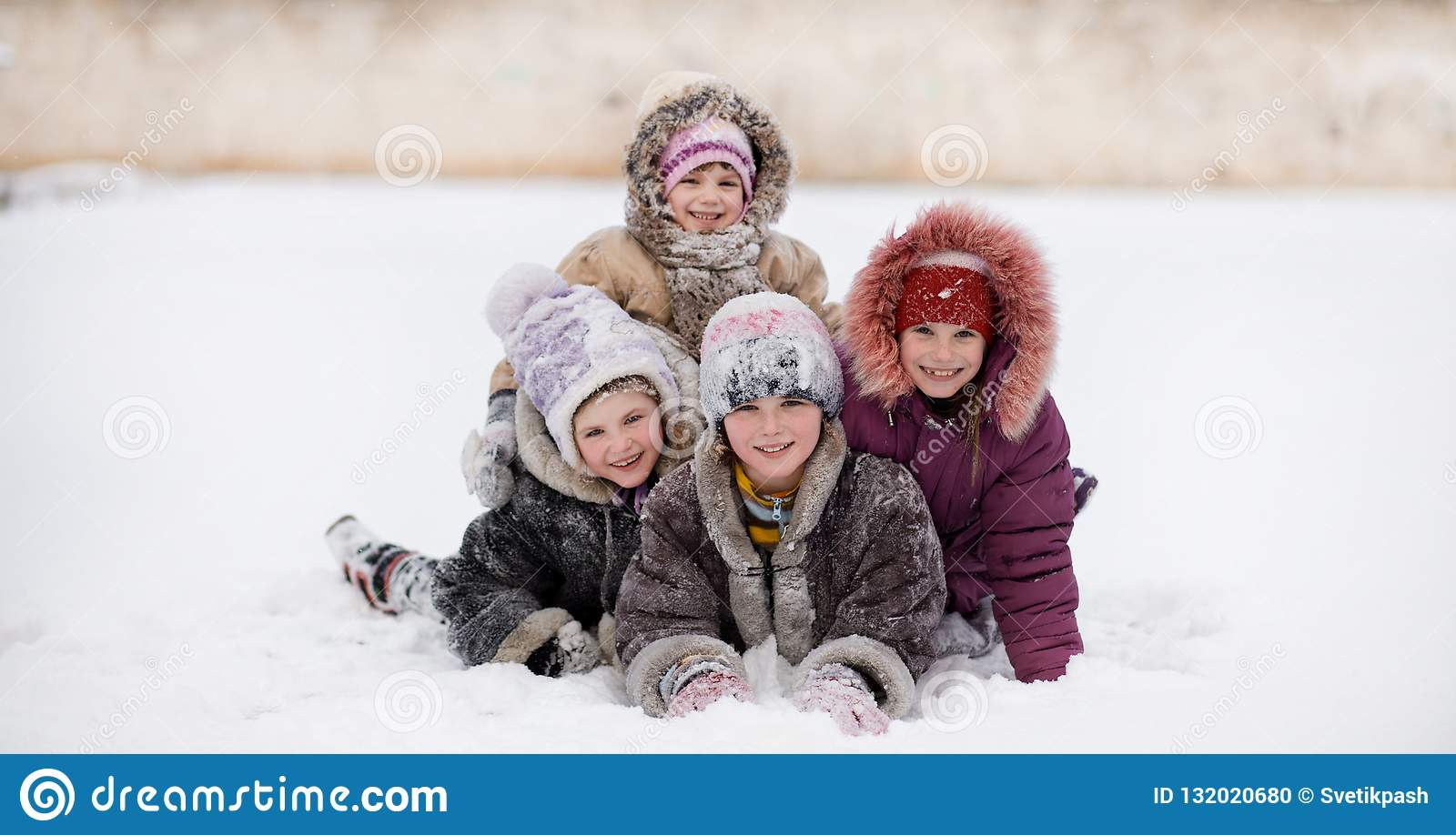 Funny children playing and laughing on snowy winter park