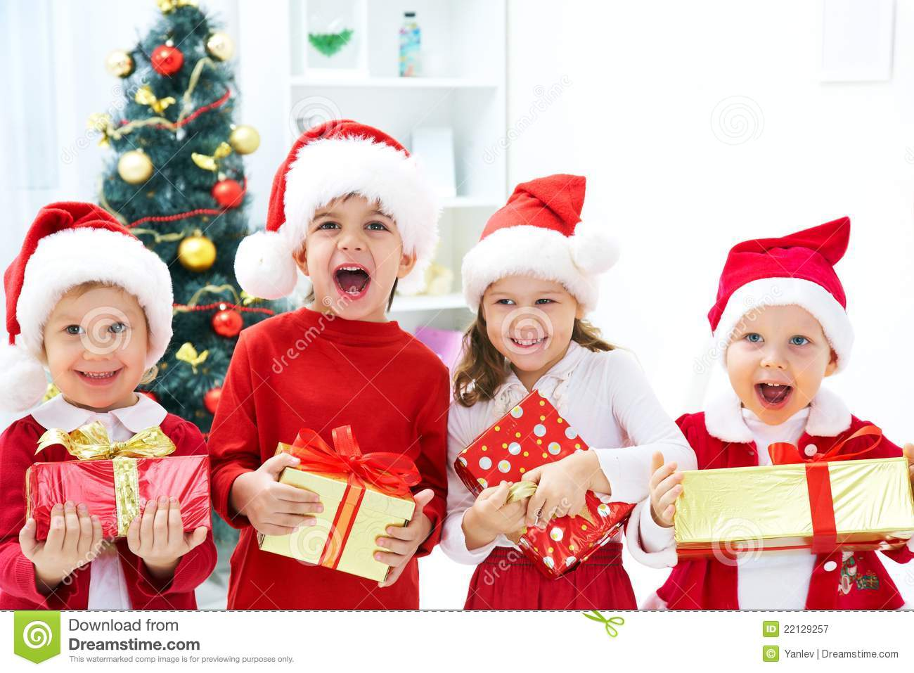 77af33b166454 Group of four children in Christmas hat with presents