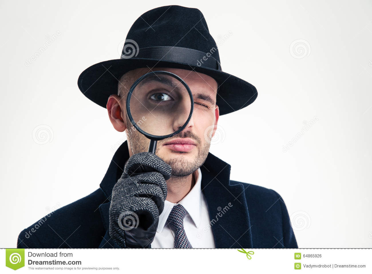 Funny concentrated inspector in black hat looking through the magnifier