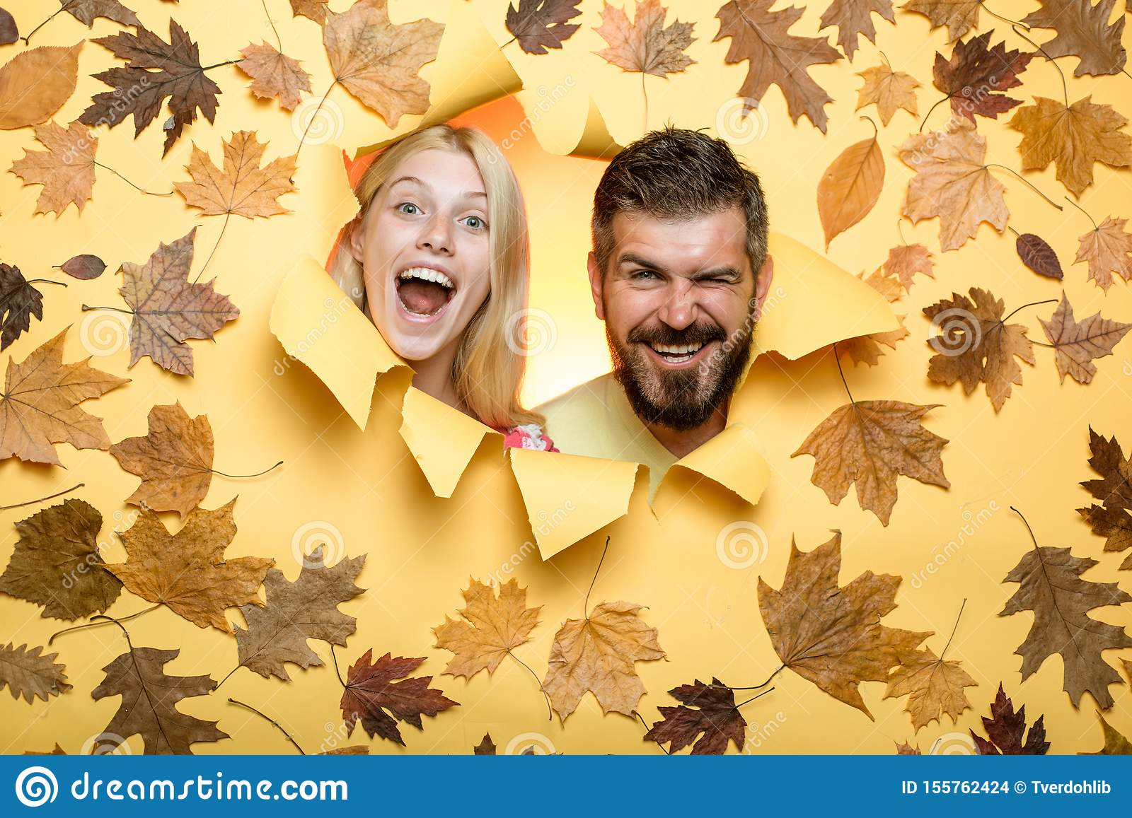 Funny couple getting ready for autumn sale. Joyful couple is happy with last warm days of autumn. Surprised couple on