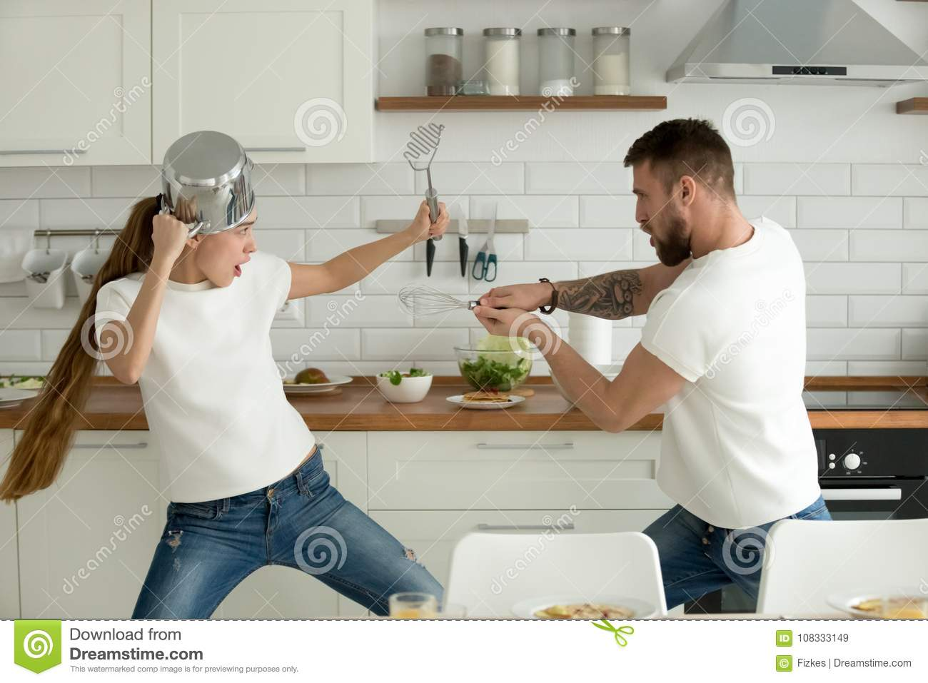 Funny Couple Having Fun Fighting With Kitchen Utensils
