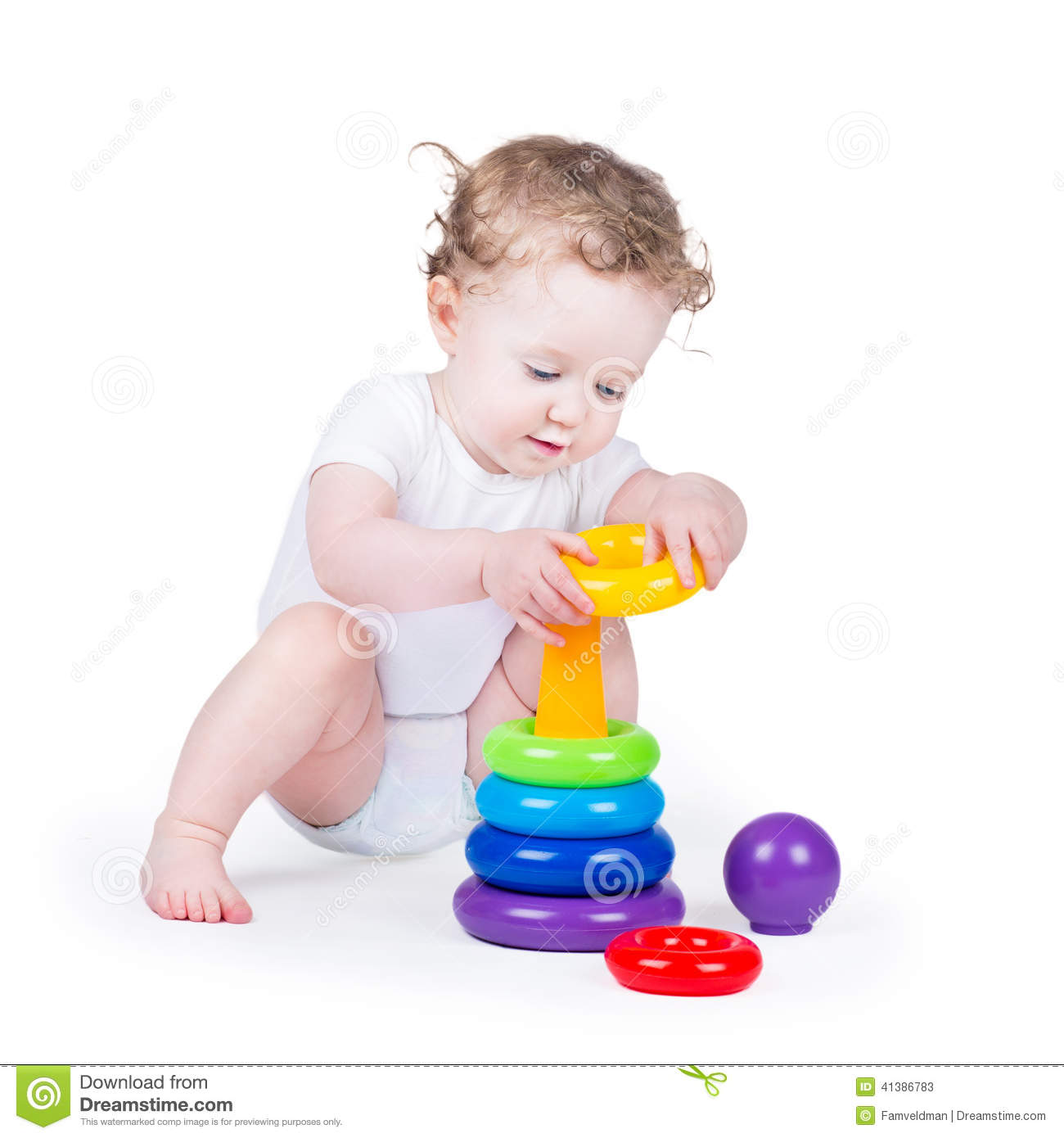 Funny curly baby girl playing with a colorful pyramid