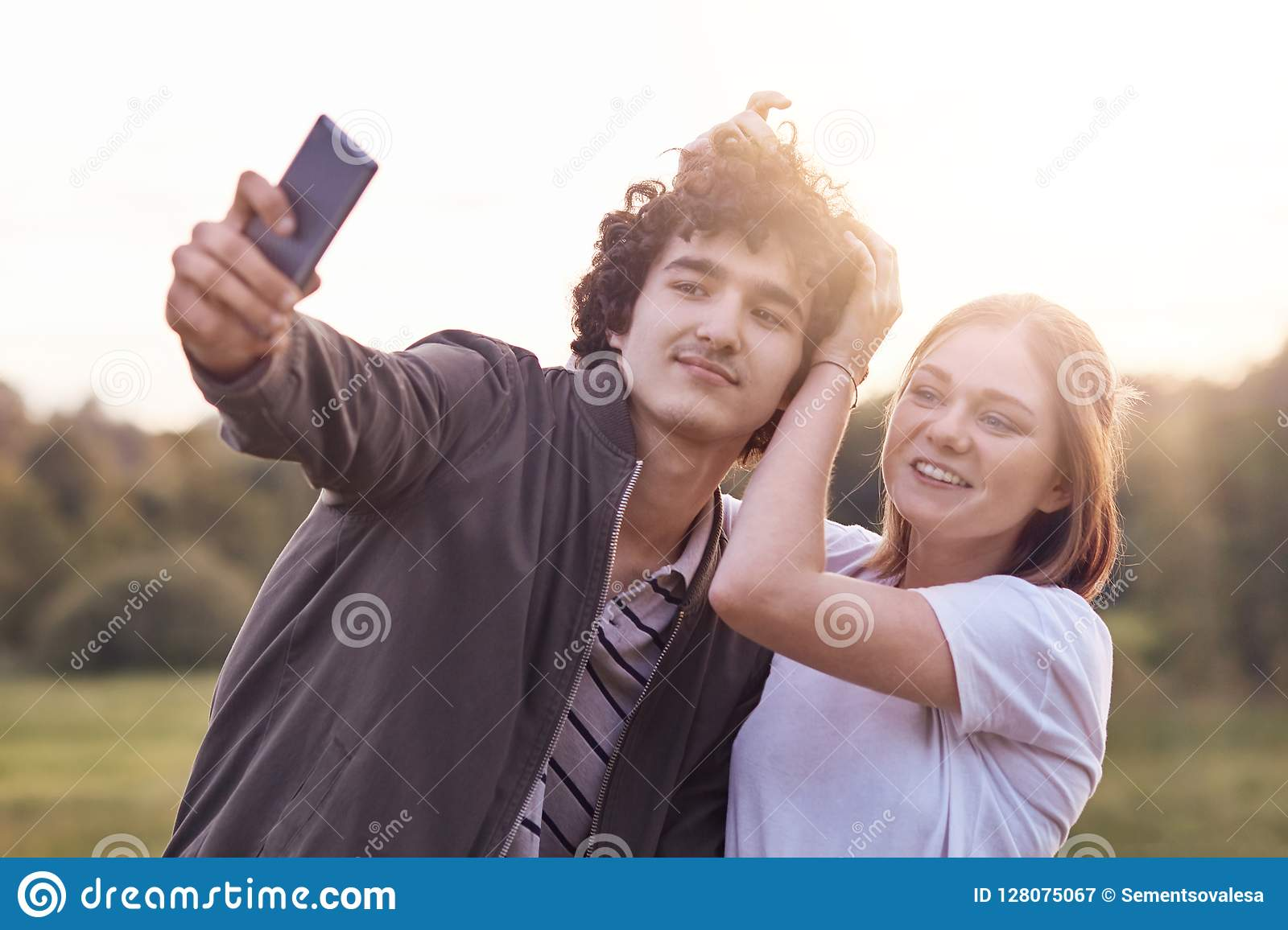 Funny Curly Male Youngster And His Girlfriend Pose For Making Selfie Portrait Against Blurred Nature Background Have Positive Exp Stock Image Image Of Girlfriend Relaxation 128075067