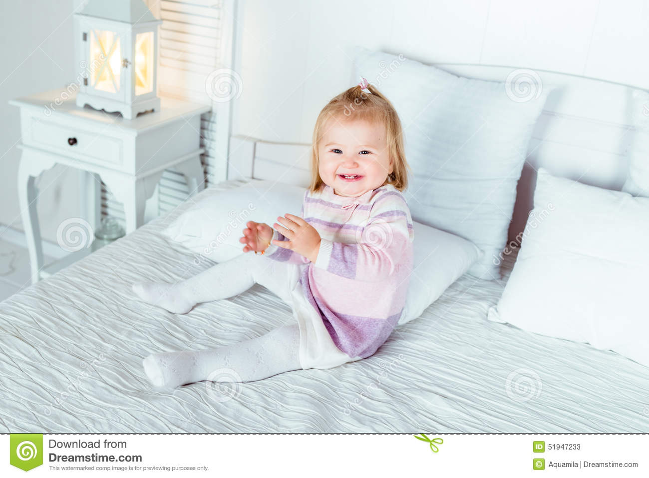 Funny And Cute Blond Little Laughing Girl Playing On Bed