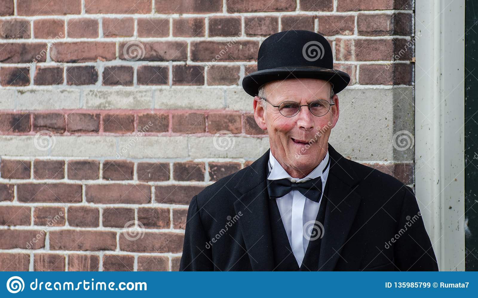 Funny dutch man with black bowler hat and glasses posing on brick wall background