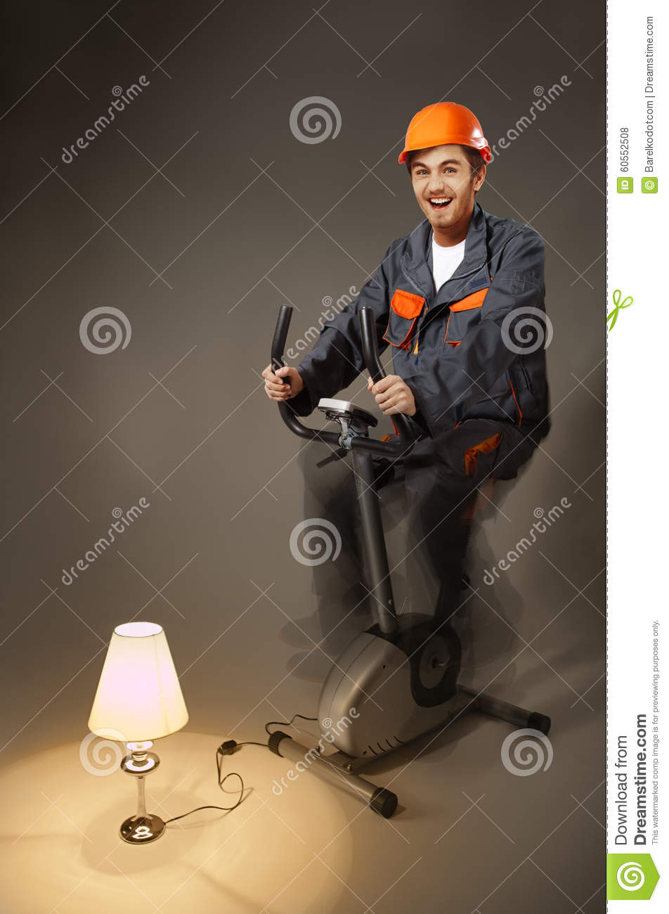 Funny electrician sitting on exercise bike generate electricity